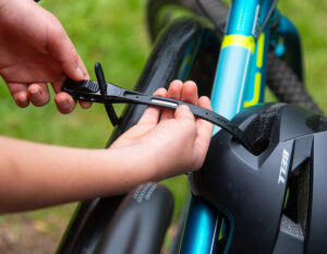 childs bicycle helmet being secured to the top tube of a childs bike with a z lok combination lock