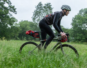 man riding through a feild on a bicycle with saddle bags holding z lok combination lock