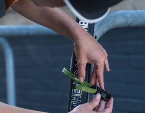 Women locking e-scooter to a bike rack with hiplok z lok combination lock