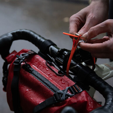 man securing a saddle bag to the handlebars of a wet bicycle