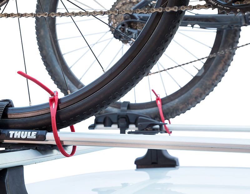 rear wheels of two bicycles attached to a roof rack on the roof of a car with z loks locking wheels to the rack