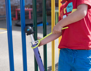 child locking a scooter to a colourful fence in a playground with a z lok