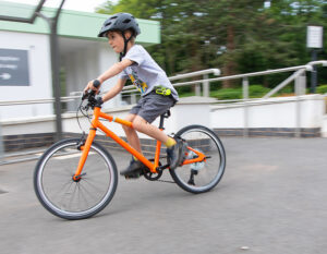 child riding a bicycle with a hiplok pop chain lock around his waist