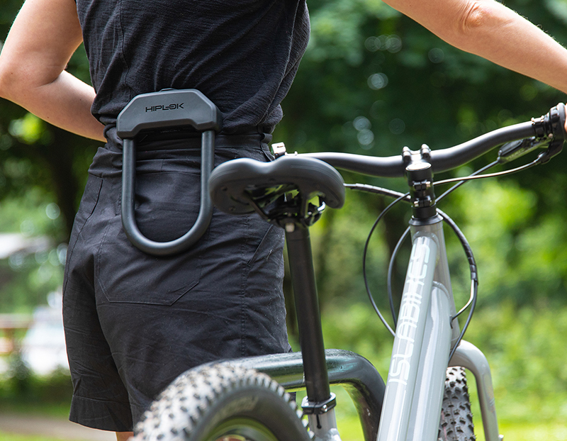 women walking with bike with a d lock clipped to the back of shorts