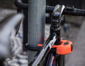 road bike locked to metal post with a d lock