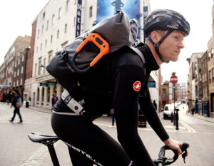 man riding through city on road bike with d lock bike lock attached to bag