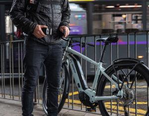e bike lent against railing man un straping wearble chain lock from waist