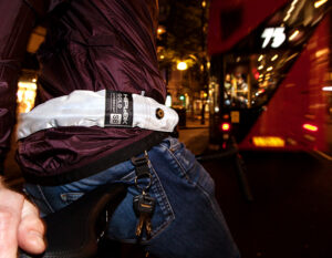 man stud over bike in a city at night with refelctive wearble chain lock around his waist