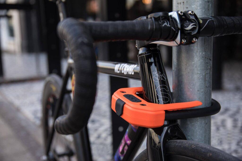 Hiplok DX orange locking headtube of fixed gear bike in a urban area around the head tube and a lamp post