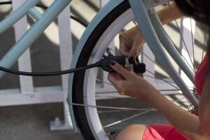 Women locking bike frame and wheel to fence with hiplok pop cable lock