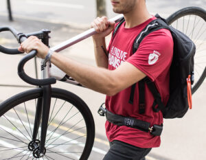 man carrying bike over his shoulder with wearble chain lock strapped around his waist