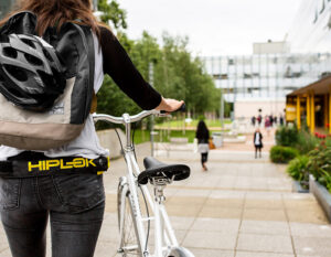 women walking bike at a univercity with a helmet strapped to rucksack and a bike chain lock strapped to her waist