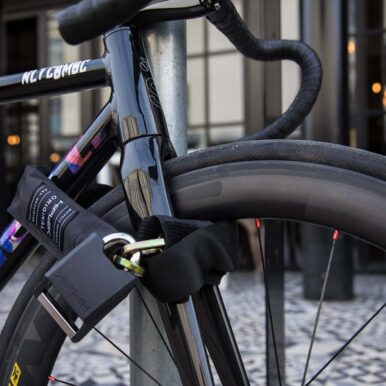 Hiplok ORIGINAL chain lock locked to a fix geard bikes front wheel and frame in a city