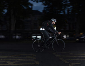 man riding on a road in the dark with wearble reflective chain lock around waist