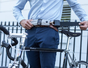 men in formal clothing strapping chain lock around waist with a bike in front