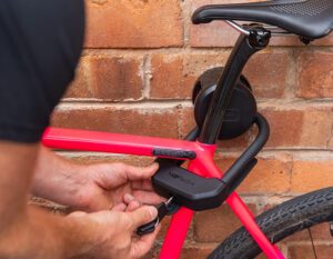 Man locking road bike to wall anchor with a key