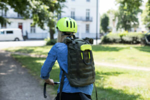 Student riding bike with lightweight Hiplok Sold Secure D Lock attached to bag
