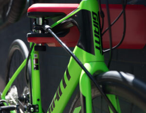 Road bike locked in AIRLOK wall hanger with a steel security cable on a black brick wall