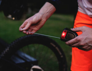 man extending cable from hiplok flx bike lock with the red saftey light on the lock turned on