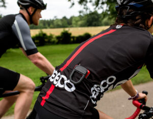 women riding a road bicycle with a hiplok fx clipped to the rear pocked of her cycling jersey