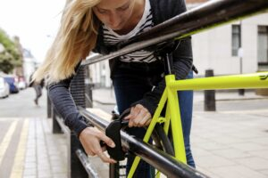 Women locking bike to railing with d lock in a town