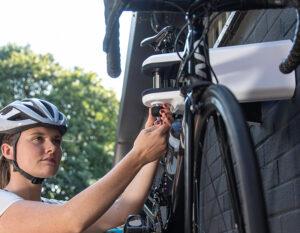 Women unlocking AIRLOK wall hanger locking pin with womens road bike in