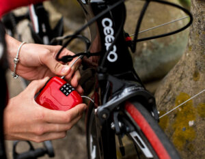 women interting the end of hiplok fx cable lock cable into locking mechanism whilst locking road bike to a stone bridge