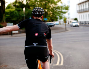 man riding a road bike with a hiplok flx cable bike lock clipped to the rear pocket of his riding jersey