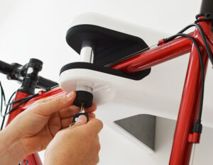 Man unlocking red road bike in AIRLOK wallhanger locking pin with a key on white wall