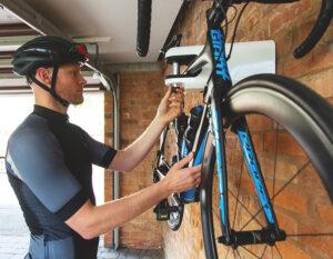 man locking road bike to Hiplok AIRLOK wall hanger in garage