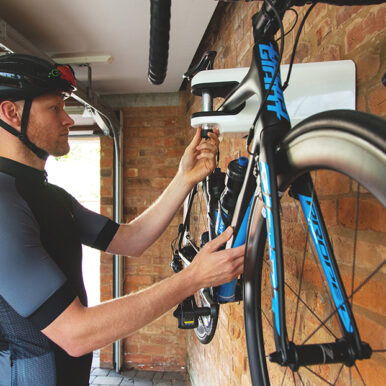 man locking road bike to Hiplok AIRLOK wall hanger in garage