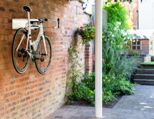 Bike locked with AIRLOK bike hanger in a garden on a brick wall