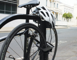 Bike locked up in a town to a metal bike rack with a D lock securing the rear wheel and frame and the security cable securing a helmet