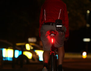 man riding road bike at night with a d lock clipped to belt with reflective strips