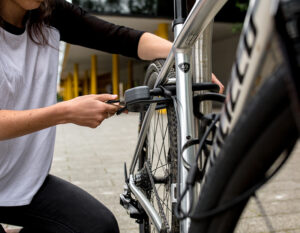 Women locking a D lock to a bike on a metal bike rack with a steel accesories cable