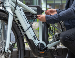 man locking electric bike to metal bike rack with d lock and steel accesories cable