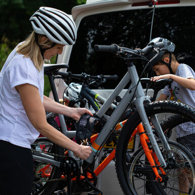 women and child locking bikes to bike rack on the back of a van with heavy duty chain lock