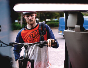 man putting mountain bike into van with a heavy duty chain lock slug over his shoulder