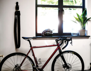 bike in a house lent against a wall with a long heavy duty chain lock hooked to the wall