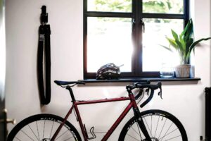 Bike lent up against a wall and window inside a house with a Hiplok Homie chain lock hung on the wall with a wall hanger