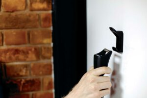 Man hooking bike chain lock to wall storage hook inside of house