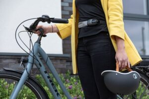 Commuter wearing yellow coat and superbright spin lock around waist, walking with bicycle