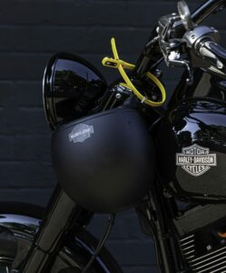 Yellow Z LOK Combo Security Tie locking black motorbike helmet to black motorbike handlebars